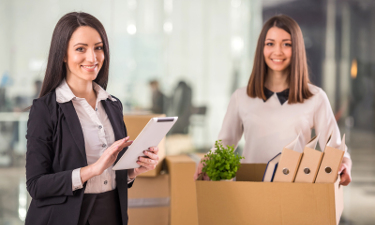 Two female businesswomen moving into a new office