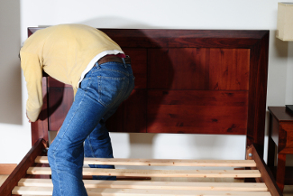 Unrecognizable person assembling a new bed in a room.